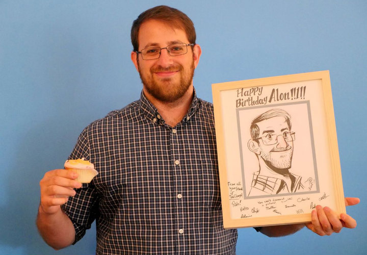 Alon with his birthday gifts from the office: cupcakes and a sketch of himself made by his co-worker Pablo