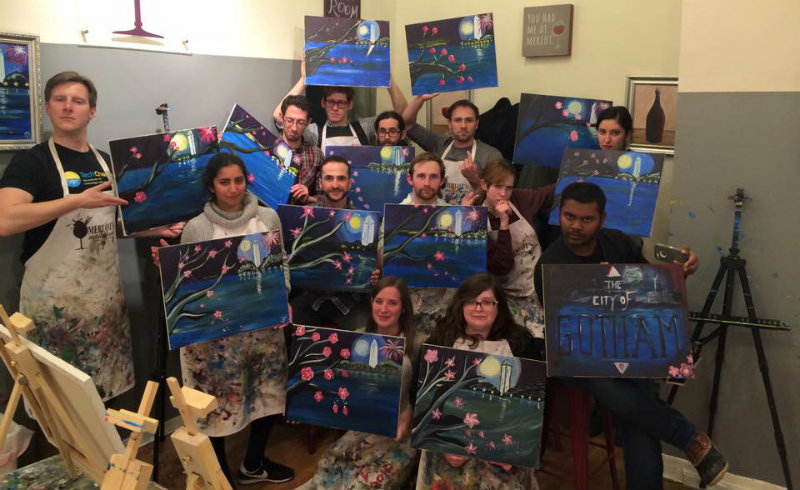The TechChange team strikes a serious artist pose with their final art pieces during Wine and Painting night